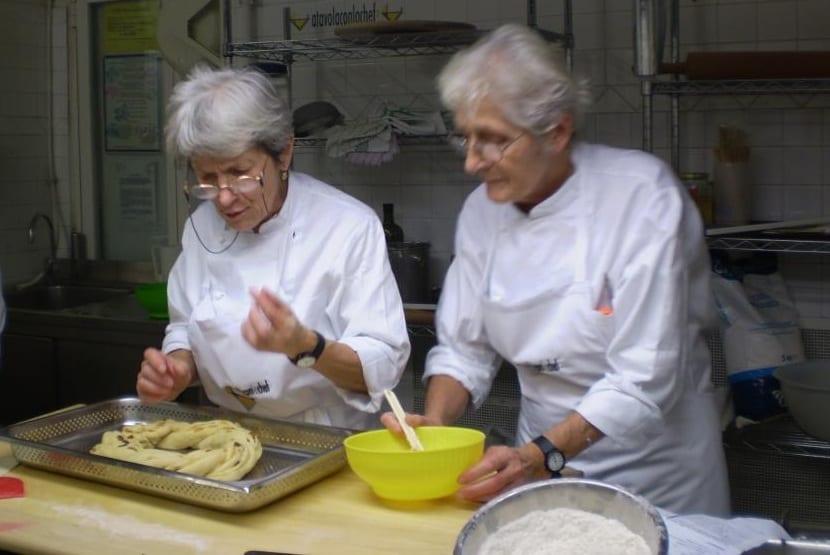 Le sorelle Simili al lavoro con un impasto in cucina