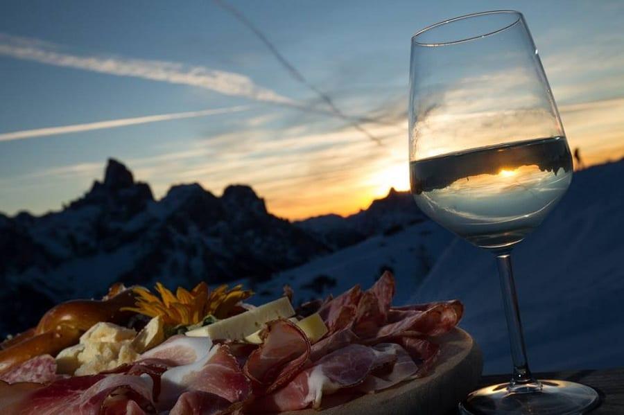 Tagliere di salumi e calice di bollicine al tramonto sulle Dolomiti innevate
