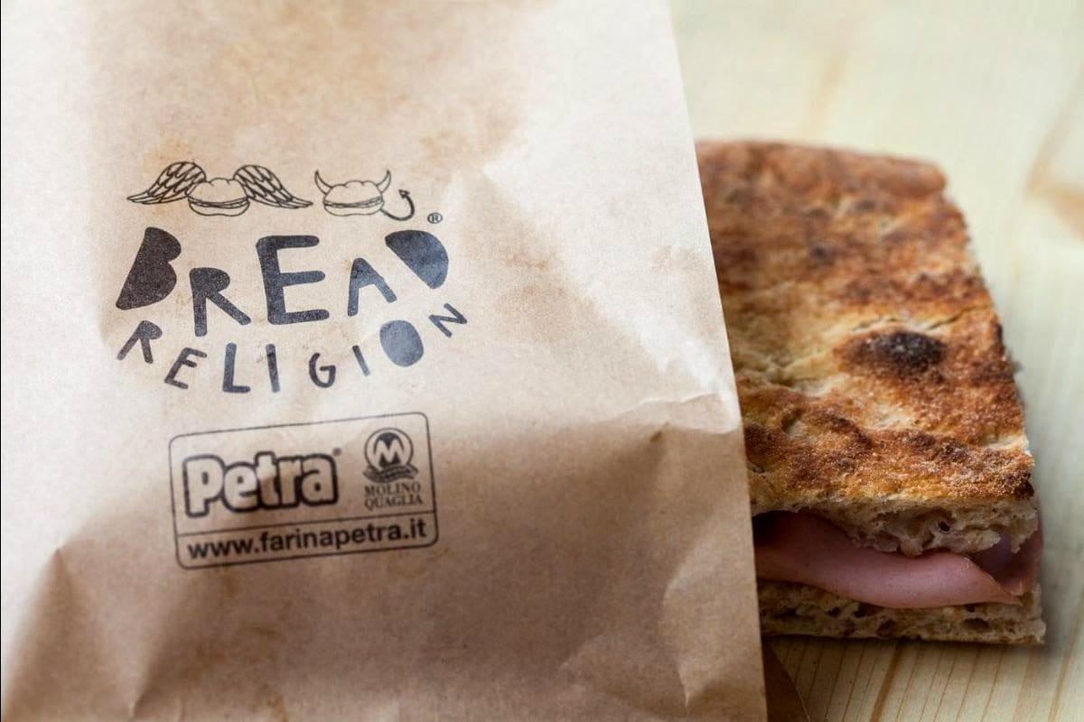 Pezzo di pizza bianca con salume avvolto in carta intestata bread religion
