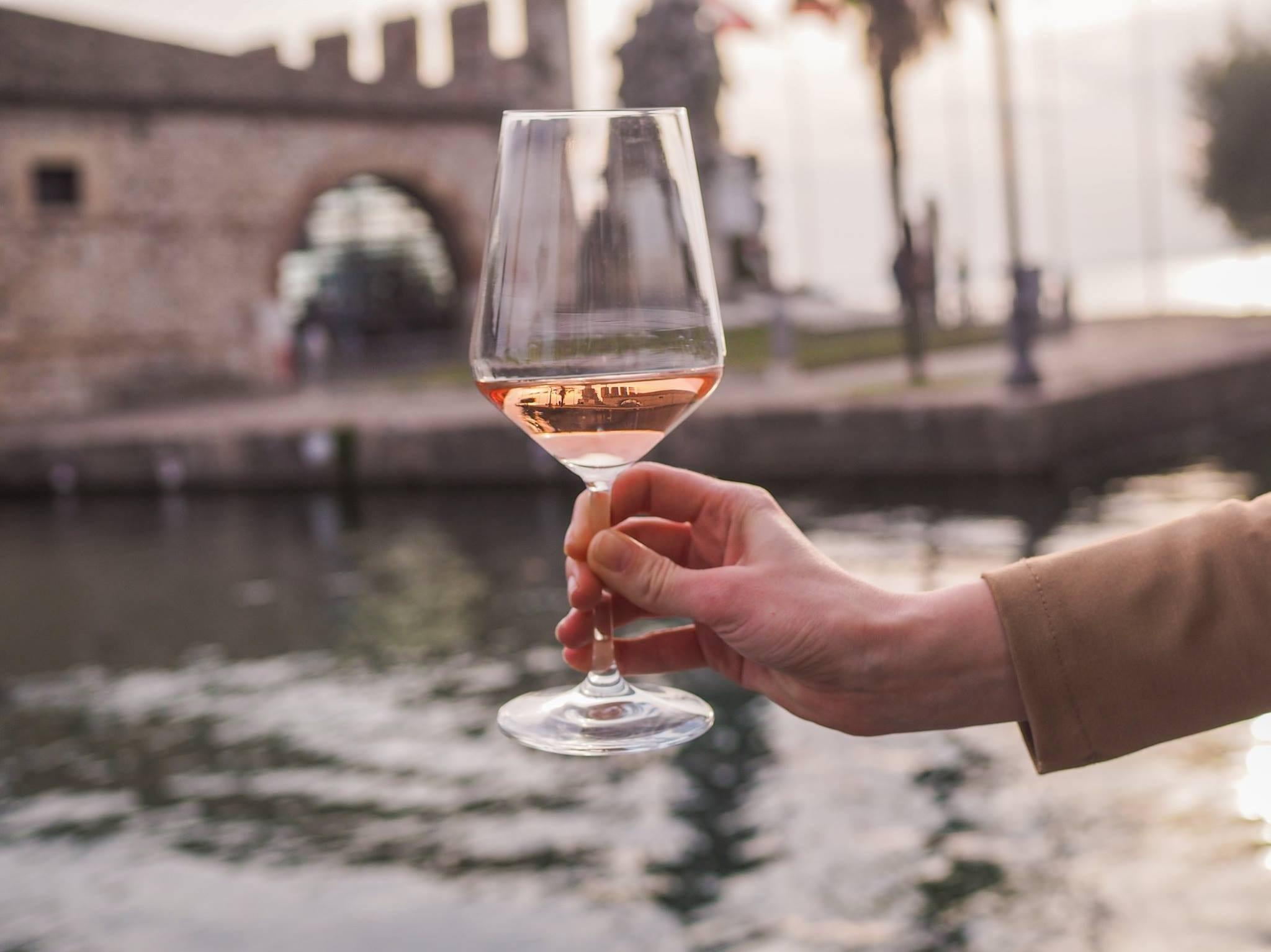 vini rosati, un bicchiere tenuto davanti a un canale